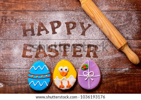 high-angle shot of a wooden table sprinkled with icing sugar or flour where you can read the text happy easter, some cookies decorated as ornamented easter eggs and a funny chick, and a rolling pin