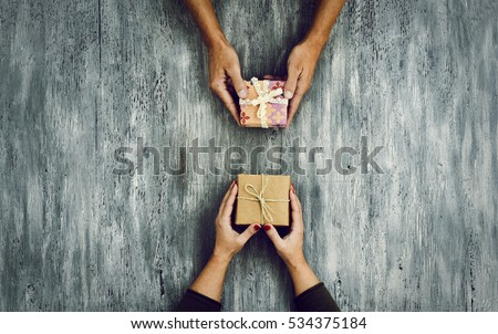 high-angle shot of a young caucasian woman and a young caucasian man exchanging gifts on a rustic wooden table, with some negative spaces around them #534375184
