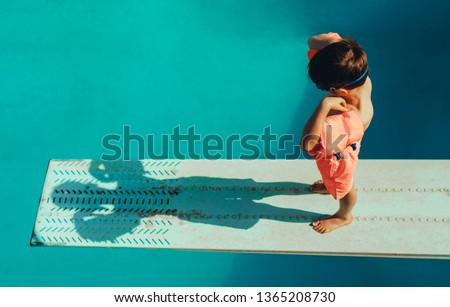High angle shot of boy with sleeves floats on diving board preparing for dive in the pool. Boy standing on spring board at the swimming pool.