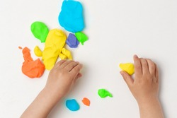 High angle shot of child playing with colorful modeling compound on the table