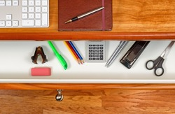 High angle shot of open desk drawer with work items inside. Red oak desktop has computer keyboard, executive notepad and pen. Wooden oak floor underneath desk.