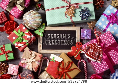 high-angle shot of some christmas ornaments, cookies, a pile of gifts tied with ribbons of different colors, and a chalkboard with the text seasons greetings written in it, on a rustic wooden surface