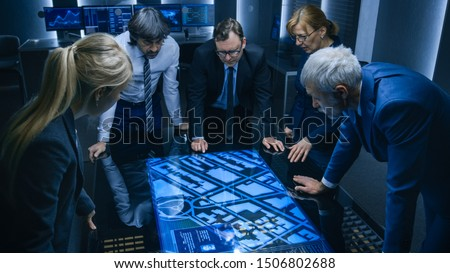 High Angle Shot of Team of Government Intelligence Agents Talking while Standing Around Digital Touch Screen Table and Tracking Suspect. Satellite Surveillance Operation in the Monitoring Room.