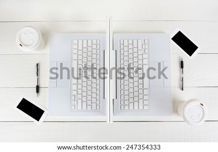 High angle shot of two laptop work stations back-to-back with mirror image identical layouts. Horizontal format on a white wood table.