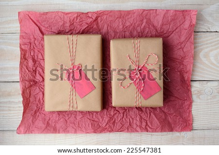 High angle shot of two plain brown paper wrapped presents on a crumpled sheet of red tissue paper. Horizontal format on a rustic white wood table.