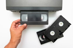 High angle shot on video tape inserted in VCR. CCTV tape recorder. Black video cassette VHS type loaded in video cassette recorder.