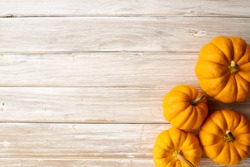 High angle still life of autumn decorative pumpkins and gourds. Horizontal format on a white wood table with copy space, Halloween and Thanksgiving concept