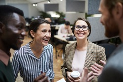 High angle view at multi-ethnic group of business people laughing happily while chatting during coffee break in office, copy space