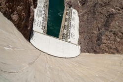 High Angle View Looking Down Curved Wall at Colorado River and Hydroelectric Equipment from top of Hoover Dam, a Popular Tourist Attraction in Black Canyon on Border of Arizona and Nevada, USA