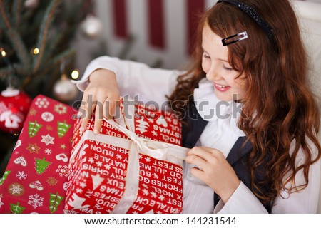 High angle view of a beautiful excited little girl unwrapping her Christmas present untying the decorative ribbon