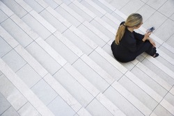 High angle view of a businesswoman using cell phone while sitting on stairs