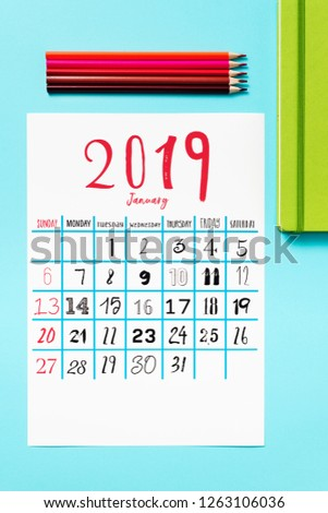 high angle view of a calendar of 2019 on a blue table, next to some pencil crayons of different colors and a green notepad #1263106036