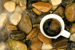 High angle view of a coffee on rocks in a stream flowing with clear water. Copy space.