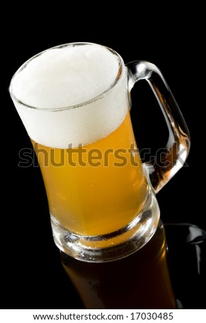 High angle view of a cold beer with moisture on the surface of the mug isolated on a black background