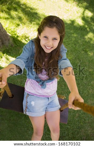 High angle view of a cute little young girl sitting on swing