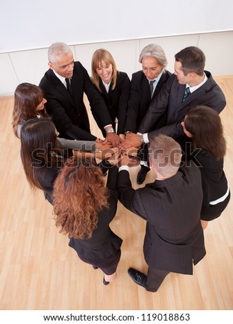 High angle view of a diverse group of people in a business team with their hands one on top of the other
