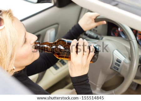 High angle view of a drunk woman driver sitting behind her steering wheel imbibing from a bottle of alcohol as she drives