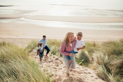 High angle view of a family walking up the sand dune from the beach.