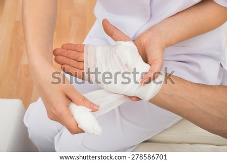 High Angle View Of A Female Doctor Bandaging Patient\'s Hand