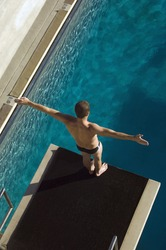 High angle view of a male diver ready to dive into the pool