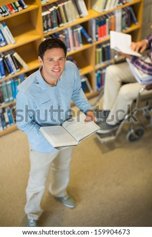 High angle view of a man by disabled student in wheelchair against bookshelf in the library