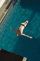 High angle view of a man diving in midair into the pool