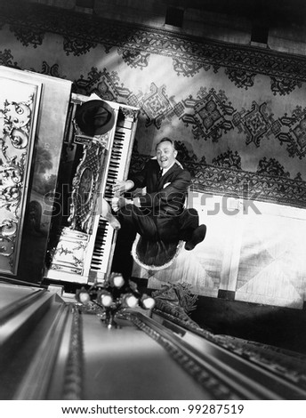 High angle view of a man reclining on a chair and playing a piano