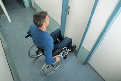 High Angle View Of A Man Sitting On Wheelchair Opening Door