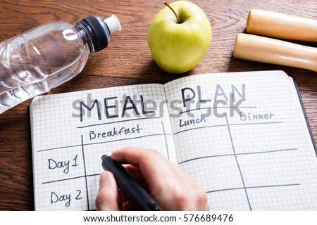 High Angle View Of A Person Hand Filling Meal Plan In Notebook At Wooden Desk