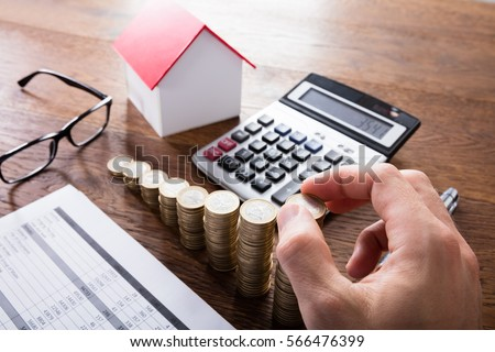 High Angle View Of A Person Stacking Coins On Wooden Desk. Property Tax Concept