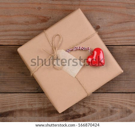 High angle view of a plain brown paper wrapped Valentines Day present with a ceramic red heart. Square format on a rustic wood surface.
