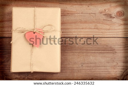 High angle view of a plain brown paper wrapped Valentines Day present with a red heart gift tag. Horizontal format on a rustic wood surface with copy space with instagram effect.