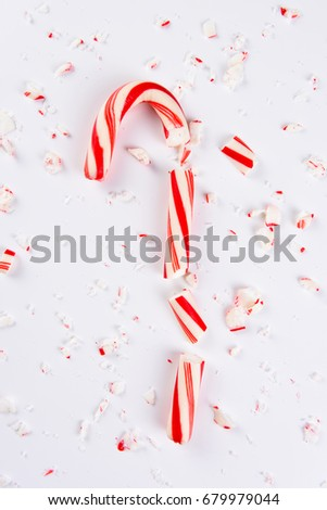 High angle view of a shattered candy cane on white.