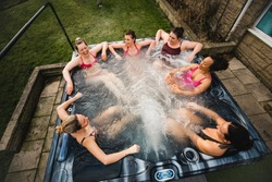High angle view of a small group of female friends relaxing in a hot tub together.