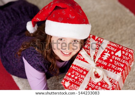 High angle view of a smiling young girl wearing a colorful red Santa hat lying on the floor with a large Christmas present looking up with a smile
