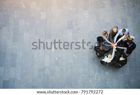Photo of High angle view of a team of united businesspeople standing with their hands together in a huddle in the lobby of a modern office building