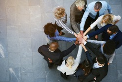 High angle view of a team of united coworkers standing with their hands together in a huddle in the lobby of a modern office building