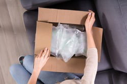 High Angle View Of A Woman's Hand Opening Delivered Parcel