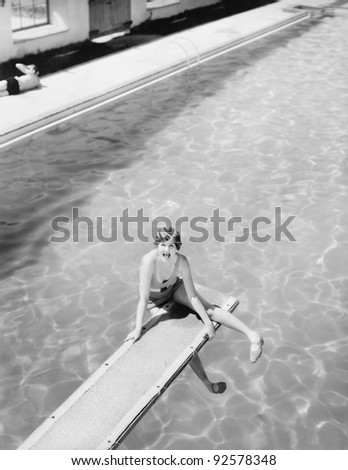High angle view of a woman sitting on a diving board and looking feared