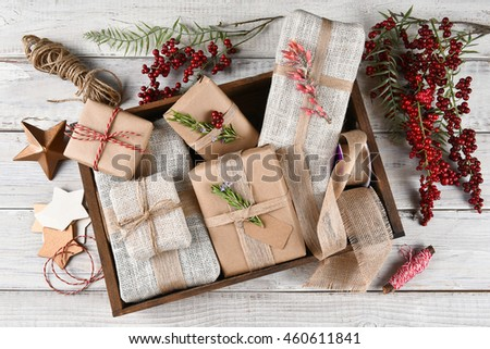 High angle view of a wood box filled with Christmas presents surrounded by wrapping tools and supplies both natural and man made. #460611841