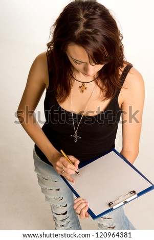 High angle view of a young female student in casual jeans writing on a clipboard with her pen placed at the end of a blank page for your text as though she were signing it