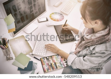 High angle view of an artist drawing something on graphic tablet at the office #548209513