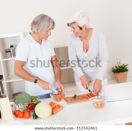 High angle view of an attractive middle-aged couple preparing a meal chopping vegetables in their kitchen
