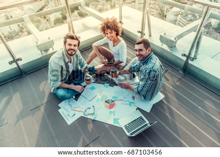 High angle view of beautiful young people drinking coffee, looking at camera and smiling while working on balcony of the city building