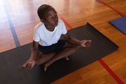 High angle view of black schoolboy doing yoga and meditating on a yoga mat in school