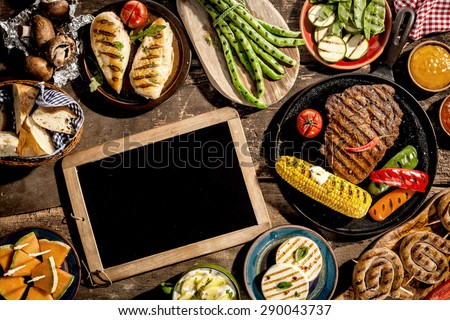 High Angle View of Blank Chalkboard Amongst Grilled Meal of Steak, Chicken and Vegetables Spread Out on Rustic Wooden Table at Barbeque Party Сток-фото ©