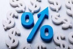 High Angle View Of Blue Percentage Symbol Surrounded By Many Dollar Currency Signs