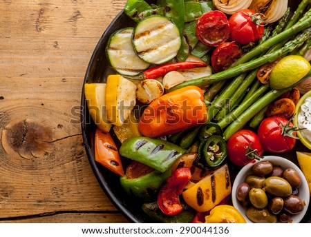 High Angle View of Bounty of Colorful Grilled Vegetables and Olives Served on Cast Iron Pan and Resting on Wooden Table Surface with Copy Space #290044136
