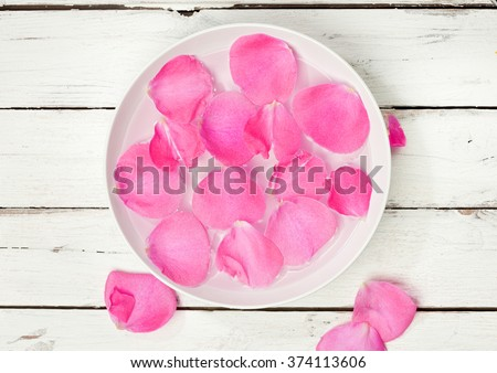 High angle view of bowl of water with pink rose petals on rustic wooden background