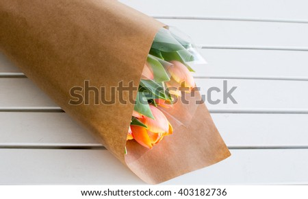 High angle view of bunch of orange tulips wrapped in brown paper laying on white table